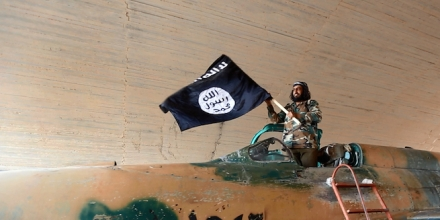 fighter of the Islamic State group waving their flag from inside a captured government fighter je
