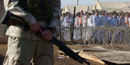 ABU GHRAIB, IRAQ - SEPTEMBER 26:  A U.S. soldier stands guard as Iraqi detainees stand in line waiting to be processed for release from Abu Ghraib prison facility on September 26, 2005 in Abu Ghraib, 21 miles west of Baghdad, Iraq. The U.S. military released about 500 detainees from Abu Ghraib prison on September 26 at the request of the Iraqi government prior to the start of the holy Muslim month of Ramadan. (Photo by Wathiq Khuzaie/Getty Images)