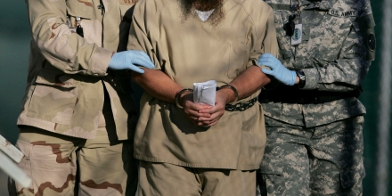 FILE - In this Dec. 6, 2006 file photo, reviewed by a U.S. Dept of Defense official, a shackled detainee is escorted while being transported inside the detention center at Guantanamo Bay U.S. Naval Base, Cuba. As the United States and its allies try to negotiate a peace settlement with the Taliban before all combat troops leave Afghanistan in 2014, a new obstacle has arisen: Insurgent splinter groups opposed to the deal are emerging, complicating U.S. hopes of leaving behind a stable country.(AP Photo/Brennan Linsley, File)