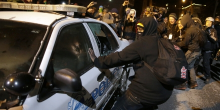 Protesters vandalize a police vehicle near Ferguson City Hall Tuesday, Nov. 25, 2014, in Ferguson, Mo. Missouri's governor ordered hundreds more state militia into Ferguson on Tuesday, after a night of protests and rioting over a grand jury's decision not to indict police officer Darren Wilson in the fatal shooting of Michael Brown, a case that has inflamed racial tensions in the U.S. (AP Photo/David Goldman)