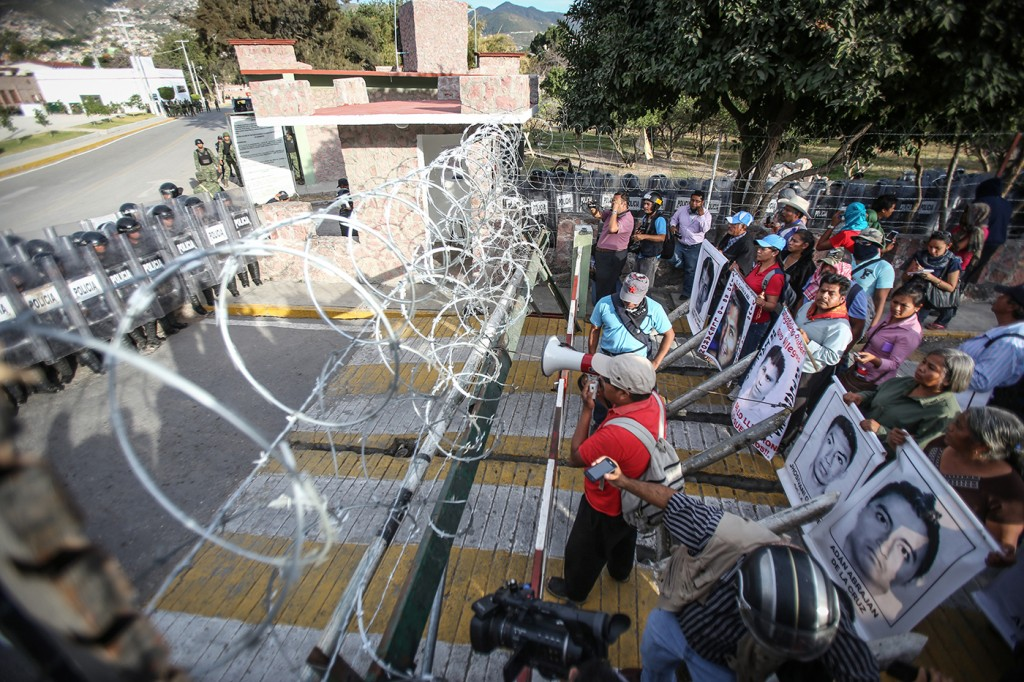 IGUALA, MEXICO - JANUARY 12: Protestors demanding justice and clarification of the disappearance of 43 students from Ayotzinapa stage clash with police in front of the 27th infantry battalion headquarters in Iguala, Mexico on January 12, 2015. Trucks are damaged and set on fire during protest. (Photo by Eric Chavelas Hernandez/Anadolu Agency/Getty Images)