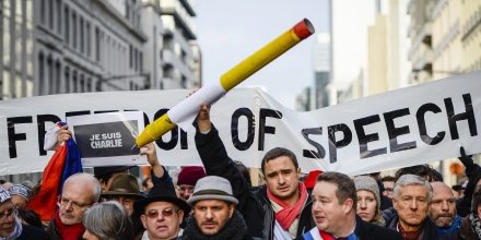 A protester holds a giant pencil next to a sign reading