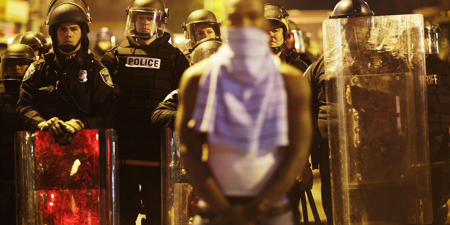 Baltimore police officers in riot gear push protestors back along - A Man Stands In Front Of A Line Of Police Officers In Riot Gear As Part