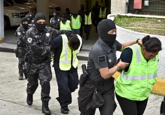 Attorney's General office's special agents custody some of the 27 municipal policemen involved in an attack against students in Iguala last month and now presented to the press in Mexico City on October 17, 2014.  More than 1,200 security forces are looking for the college students around Iguala, where the aspiring teachers were last seen on September 26, when local police allegedly attacked them and turned them over to the Guerreros Unidos gang.    AFP PHOTO/Yuri CORTEZ        (Photo credit should read YURI CORTEZ/AFP/Getty Images)