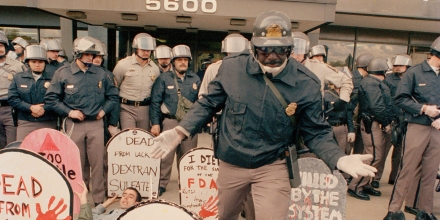 Demonstrators from the organization ACT UP, angry with the federal government's response to the AIDS crisis, protest in front of the headquarters of the Food and Drug Administration in Rockville, Md., Oct. 11, 1988, and effectively shut it down. A police officer steps into the group and by mid-morning some 50 of the protesters were arrested. (AP Photo/J. Scott Applewhite)