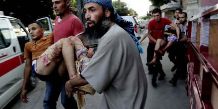 FILE - In this July 30, 2014 file photo, Palestinians carry injured people to ambulances following Israeli airstrikes in the Shijaiyah neighborhood of Gaza City. The Israeli strike along the border with Israel, came at the height of the fighting and was one of the deadliest single incidents during the entire conflict. Because of the heavy casualty toll, Israel's Military Advocate General launched an investigation into the Shijaiyah incident. The probe cleared the military personnel of any wrongdoing, finding no evidence of criminal misconduct. (AP Photo/Adel Hana, File)
