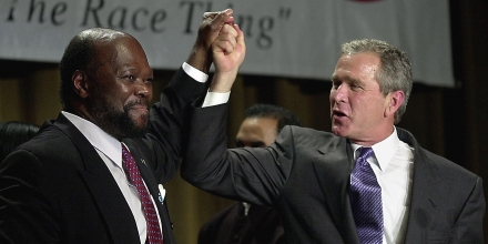 NEW YORK, UNITED STATES:  Roy Innis (L), National Chairman of the Congress of Racial Equality, holds up the hand of Texas Governor and US Presidential Candidate George W. Bush (R) at the group's Harmony Awards 26 June 2000 in New York. (ELECTRONIC IMAGE) AFP PHOTO/Stan HONDA (Photo credit should read STAN HONDA/AFP/Getty Images)