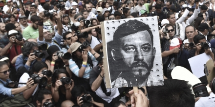 Mexican photojournalists hold pictures of their murdered colleague Ruben Espinosa during a demonstration held at the Angel of  Independence square in Mexico City, on August 2, 2015. Espinosa was found shot dead on August 1, 2015, in Mexico City, where he had moved two months ago from Veracruz, after reporting strong threats from the government of the state. Since 2010, 11 journalists have been killed and four others have gone missing in Veracruz. AFP PHOTO/ Yuri CORTEZ        (Photo credit should read YURI CORTEZ/AFP/Getty Images)