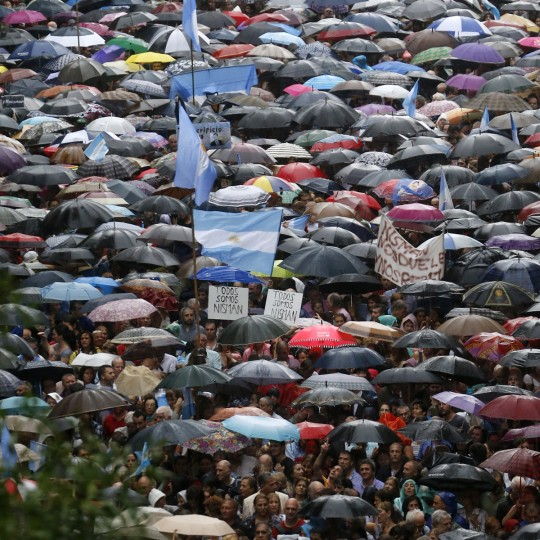 Image #: 35032471    Protesters holding umbrellas to shield themselves from the rain take part in a silent march to honour late state investigator Alberto Nisman in Buenos Aires February 18, 2015. Tens of thousands of Argentines are expected to march in silence through Argentina's capital, Buenos Aires, on Wednesday evening to honour Alberto Nisman, a state investigator who was poised to detail evidence behind his accusations that Argentine President Cristina Fernandez plotted to cover up his investigation into a 1994 bombing. Nisman was found dead with a single bullet to the head on January 18. REUTERS/Enrique Marcarian (ARGENTINA - Tags: POLITICS CIVIL UNREST CRIME LAW)       REUTERS /ENRIQUE MARCARIAN /LANDOV
