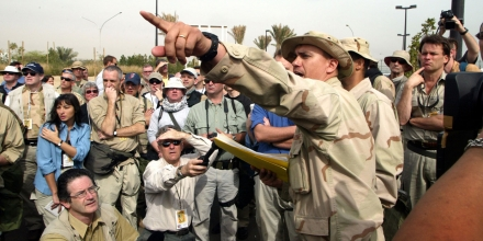 KUWAIT CITY - MARCH 11: Journalists listen to directions to their bus which will transport them to their embed site March 11, 2003 in Kuwait City. More than 600 journalists are being embedded in military units to cover a possible war with Iraq. (Photo by Joe Raedle/Getty Images)