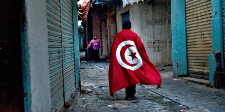 TUNIS, TUNISIA - FEBRUARY 26: A protester wearing a Tunisian flag, makes his way past closed shops in the Casbah toward sporadic gunfire in Tunis, Tunisia, on Saturday, February 26, 2011.  (Photo by Nikki Kahn/The Washington Post)