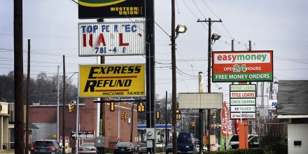 Signage advertising short-term loans stands in front of stores in Birmingham, Alabama, U.S., on Tuesday, Feb. 10, 2015. In Alabama, the sixth-poorest state, with one of the highest concentrations of lenders, advocates are trying to curb payday and title loans, a confrontation that clergy cast as God versus greed. They have been stymied by an industry that metamorphoses to escape regulation, showers lawmakers with donations, packs hearings with lobbyists and has even fought a common database meant to enforce a $500 limit in loans. Photographer: Gary Tramontina/Bloomberg via Getty Images