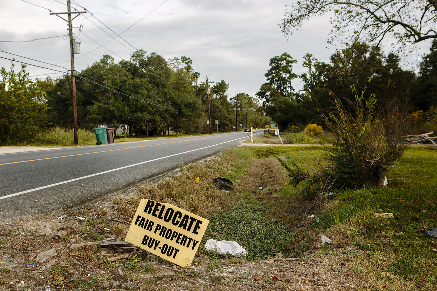 A sign advertising fair property buyouts is posted on the side of a road in the small hamlet of Mossville, Louisiana, Oct. 22, 2015.