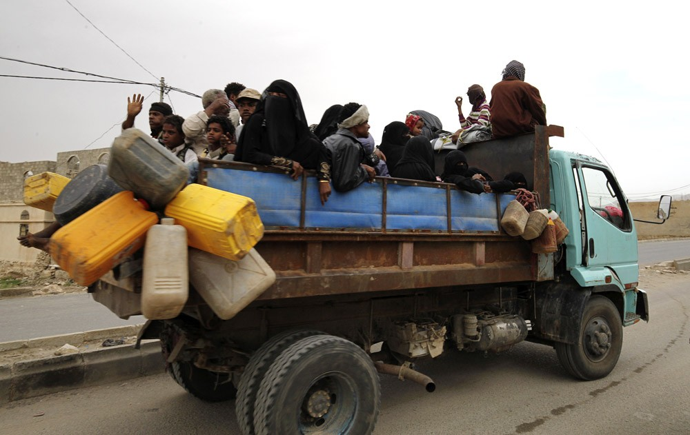 Image #: 36701899    Internally displaced people ride on the back of a truck as they flee in the district of Khamir of Yemen's northwestern province of Amran May 9, 2015. They were forced to leave their homes in the nearby province of Saada amid Saudi-led air strikes. REUTERS/Mohamed al-Sayaghi /LANDOV