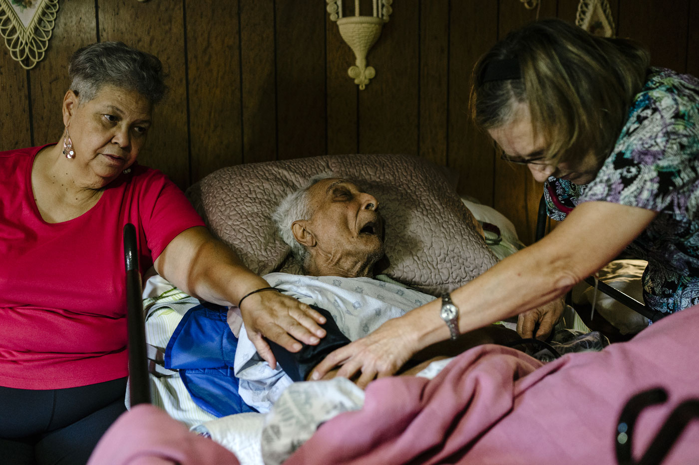 Judy Montgomery (L), 65, sits next to her father, Vallery Montgomery, 89, as nurse Laura Bull performs a checkup, Oct. 22, 2015, Westlake, La.