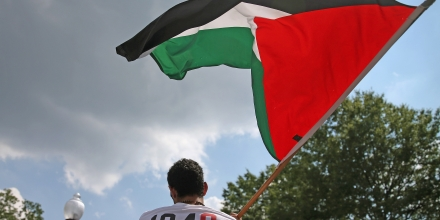 WASHINGTON, DC - JULY 11: A man who wished not to be identified waves a Palestinian flag while protesting the Israeli bombing of Gaza during a protest in front of the Israeli Embassy on July 11, 2014 in Washington, DC.  Several peace groups gathered to protest in front of the embassy to call for an end to Israel's bombing of Gaza.  (Photo by Mark Wilson/Getty Images)