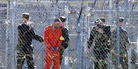 Guantanamo Bay, CUBA:  FOR USE WITH AFP STORIES: US-attacks-UN-Guantanamo (FILES) This 17 January, 2002, file photo shows a detainee (2nd L) wearing an orange jump suit surrounded by heavy security at the US Guantanamo Naval Base in Cuba. UN experts said on 16 February, 2006, the US must shut down the detention center without delay and release or try its inmates. The demand came in a report by five independent experts who act as monitors for the UN Human Rights Commission. The document charged that US treatment of the more than 500