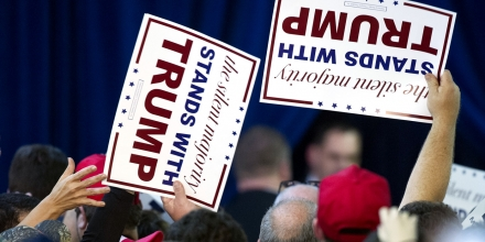 Supporters hand-out signs during Republican presidential candidate Donald Trump's campaign rally at the Prince Willam County Fair Ground in Manassas, Va., Wednesday, Dec. 2, 2015. (AP Photo/Cliff Owen)