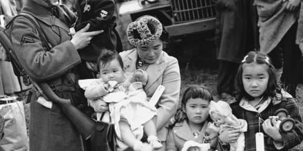 Mrs. Shigeho Kitamoto had no time for tears when she was evacuated along with other Japanese from Bainbridge Island in Washington State, March 30, 1942. She has too busy looking after her four children.  Corporal George Bushy, member of the military guard which supervised the departure of 237 Japanese for California, gave her a hand with the youngest.  (AP Photo)