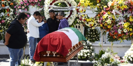 Family members of the slain mayor of Temixco, Gisela Mota, mourn next to her casket, during a ceremony in her honor, at the mayor's office building of Temixco, Mexico, Sunday, Jan. 3, 2016. Mota took office as mayor of the city of on Jan. 1 and was shot at her home on Jan. 2. The governor of the southern Mexican state of Morelos says the killing of the mayor was a warning by drug gangs, meant to convince other officials to reject state police control of local forces. (AP Photo/Tony Rivera)