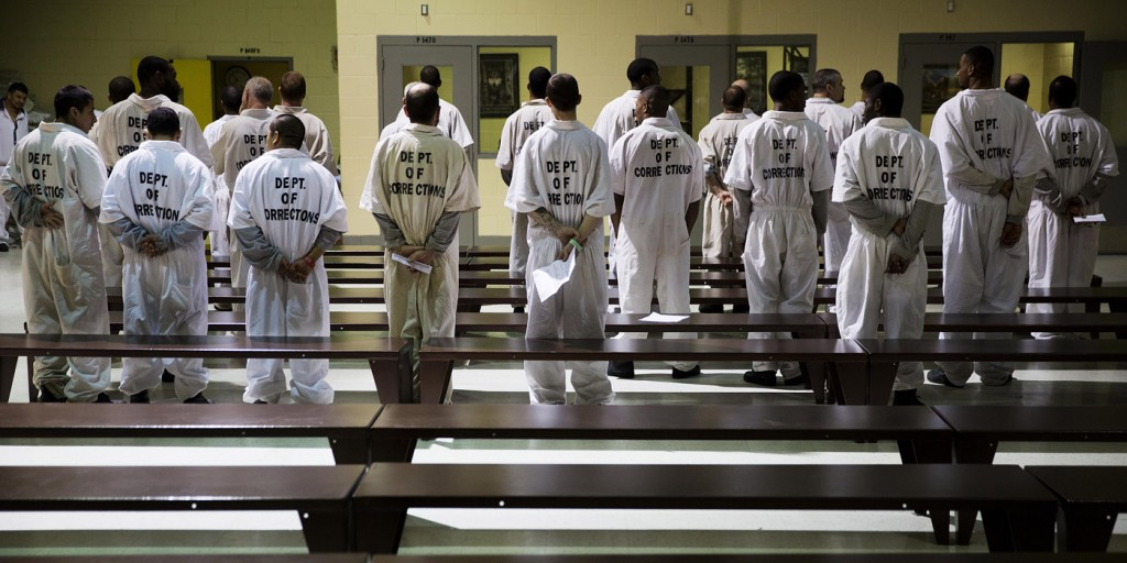 Prisoners stand while being processed for intake at the Georgia Diagnostic and Classification Prison Tuesday, Dec. 1, 2015, in Jackson, Ga. They arrive by the busload each Tuesday and Thursday, dozens of new inmates entering Georgia's prison system. Most stay only a week or two. But for those sentenced to die, this is their last stop. (AP Photo/David Goldman)
