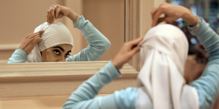 ** FILE ** Sadaf Butt, of Alabama, adjusts her hijab in a mirror at the 43rd annual Islamic Society of North America convention, Sept, 1, 2006, in Rosemont, Ill.   Earlier this year on an Arabic Web site, a Muslim woman scholar posted an open letter to the Islamic world for women to take off the veil _ that head scarves and other coverings for women are not mandated by the Quran or Islamic tradition. (AP Photo/M. Spencer Green)
