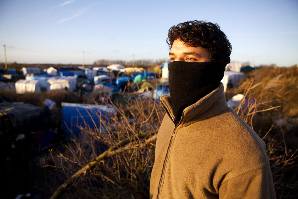 "Mohammad Qasim, 14, whose father was a contractor for the US military in Afghanistan, is seen in the refugee camp known as ""The Jungle"" in Calais, France, 04 December 2015. Conditions are deteriorating rapidly in the camp of an estimated 6,000 people as winter approaches, increasing the desperate attempts to break though fences and stowaway on trucks or trains, attempts that have seen 18 refugees die since June 2015. (John D McHugh/Verifeye Media)"