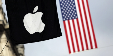 A U.S. flag flies beyond an Apple Inc. logo displayed outside the company's store on Regent Street in London, U.K., on Tuesday, Oct. 15, 2013. Burberry Group Plc named Christopher Bailey as chief executive officer to succeed Angela Ahrendts who will leave in 2014 to work as a senior vice president at Apple. Photographer: Chris Ratcliffe/Bloomberg via Getty Images