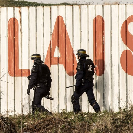 French riot police officer walk in front of a fence with the lettering 'Calais' near the A16 motorway near the site of the Eurotunnel in Coquelles, near Calais, northern France on January 21, 2016.
