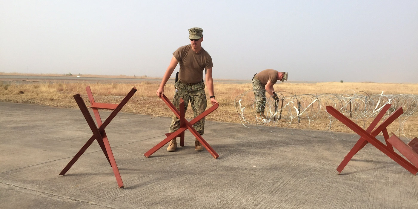 151224-N-ZZ999-001 GAROUA, Cameroon (Dec. 24, 2015) Construction Electrician 2nd Class Nolan Long, from Livingston, Texas, left, and Utilitiesman 1st Class Kenna Runyon, from Morgantown, W.Va., both assigned to Naval Mobile Construction Battalion 1, replace C-wire with hedge hogs and tie them together with towing cable to be used as soft anchors at an entry control point in Garoua, Cameroon, Dec. 24, 2015. U.S. 6th Fleet, headquartered in Naples, Italy, conducts the full spectrum of joint and naval operations, often in concert with allied, joint, and interagency partners, in order to advance U.S. national interests and security and stability in Europe and Africa. (U.S. Navy photo by Lt. j.g. Jason McGee/RELEASED)