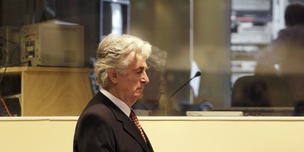 Former Bosnian Serb leader Radovan Karadzic, enters  the courtroom to enter pleas to 11 charges including genocide and crimes against humanity, at the U.N. Yugoslav war crimes tribunal in the Hague, Netherlands, Friday Aug. 29, 2008. Karadzic  refused to enter pleas to the 11 charges, including genocide and crimes against humanity, filed against him at the U.N.'s Yugoslav war crimes tribunal. After Karadzic's refusal to plead Friday, tribunal judge Iain Bonomy entered not guilty pleas on Karadzic's behalf. (AP Photo/ Valerie Kuypers, Pool)