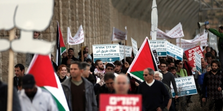 Israeli and Palestinian peace activists carry placards as they wave a Palestinian national flag during a peace march at an Israeli road near a checkpoint between the West Bank city of Beit Jala and Jerusalem on January 15, 2016.Peace activists called for this march under the slogan