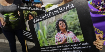 A woman holds a picture of Honduran Human Rights activist, Coordinator of the Civil Council of Popular and Indigenous Organizations of Honduras (COPINH) Berta Caceres Flores, reading