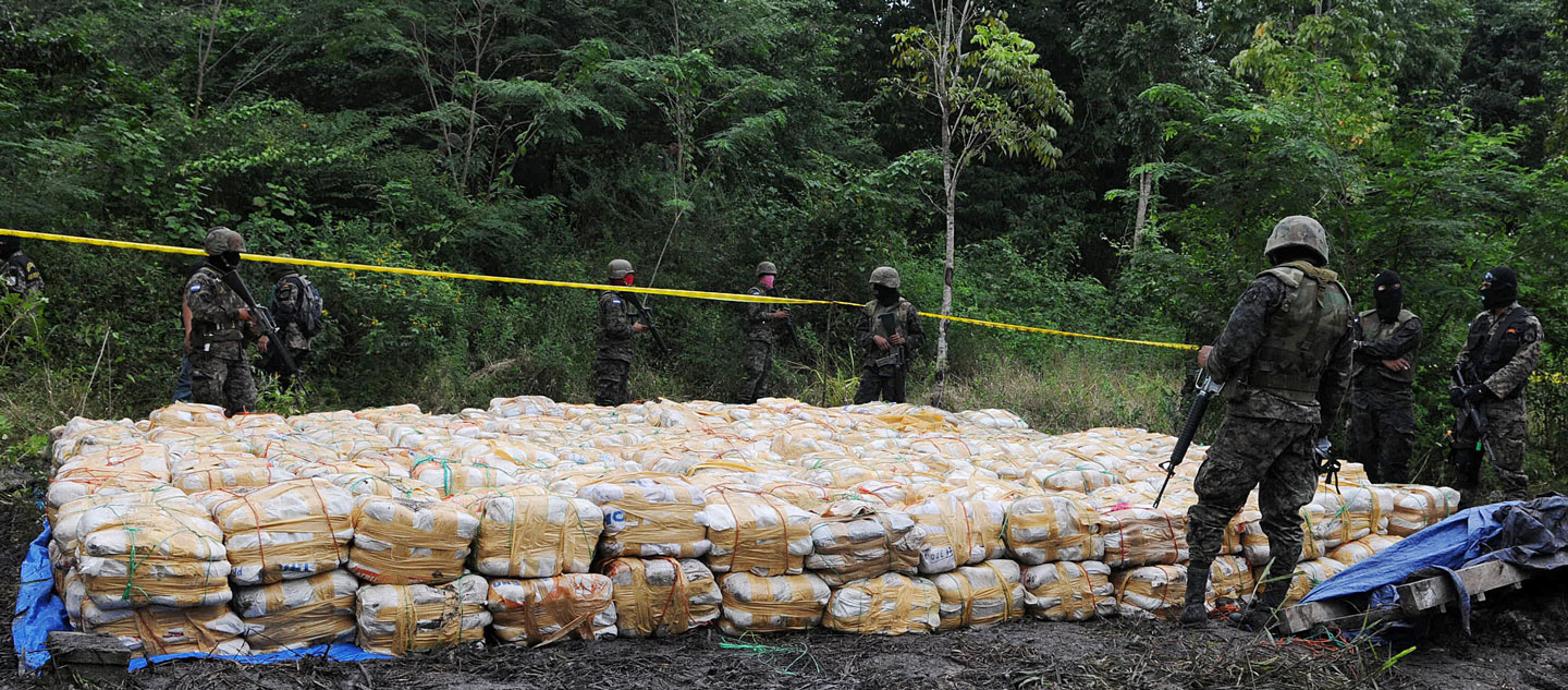 Honduran soldiers guard 15 tons of seized cocaine in Patagallina, Santa Rita municipality, Yoro department, some 300 kms north of Tegucigalpa, on November 29, 2012. The drug -found in an underground vault that operated as a laboratory- was divided into 344 packs. AFP PHOTO/STR        (Photo credit should read STR/AFP/Getty Images)