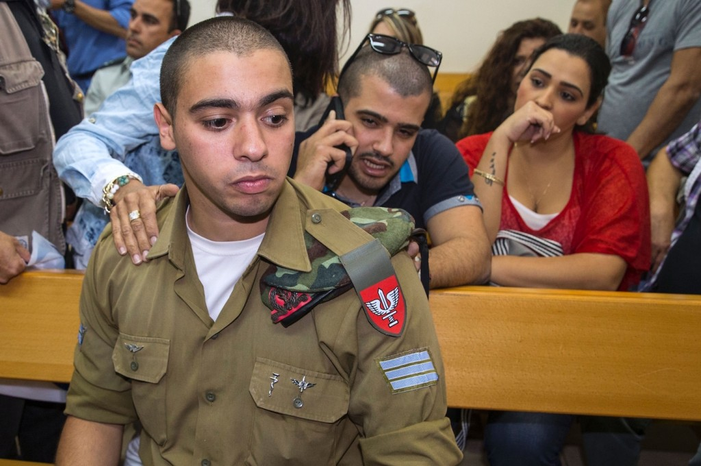 Israeli soldier Elor Azaria, who was caught on video shooting a wounded Palestinian assailant in the head as he lay on the ground, sits during a hearing at a military appeals court in Tel Aviv during which he was charged with manslaughter on April 18, 2016.Prosecutors presented the indictment to a military court over the March 24 killing, which occurred minutes after the Palestinian had stabbed another soldier and lay prone on the ground wounded by gunfire, according to Israeli authorities. He was also charged with conduct unbecoming of his rank and position in the army. / AFP / JACK GUEZ (Photo credit should read JACK GUEZ/AFP/Getty Images)