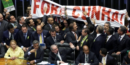 Pro-government deputies hold a banner that reads in Portuguese