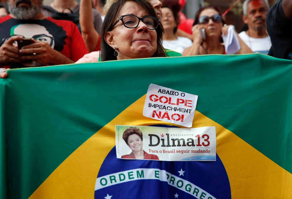 """A demonstrator holds a Brazilian flag with a sticker that reads in Portuguese """"Down with the coup, impeachment no"""" during a protest in support of Brazil's President Dilma Rousseff and former President Luiz Inacio Lula da Silva in Sao Paulo, Brazil, Thursday, March 31, 2016. Rousseff is currently facing impeachment proceedings as her government faces a stalling national economy and multiple corruption scandals. Lula da Silva has been linked to a sprawling corruption scandal involving Brazilian oil giant Petrobras. (AP Photo/Andre Penner)"""
