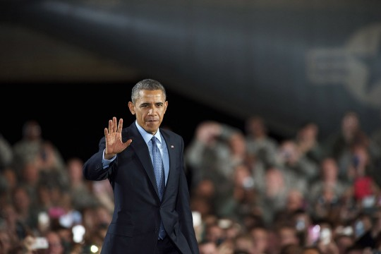JOINT BASE MCGUIRE-DIX-LAKEHURST, NEW JERSEY - DECEMBER 15:  U.S. President Barack Obama waves as he takes the stage to address an audience of armed forces December 15, 2014 at Joint Base McGuire-Dix-Lakehurst, New Jersey. Obama will address the troops to thank them for their service and mark the end of the combat mission in Afghanistan. ahead of the upcoming holidays.  (Photo by Mark Makela/Getty Images)