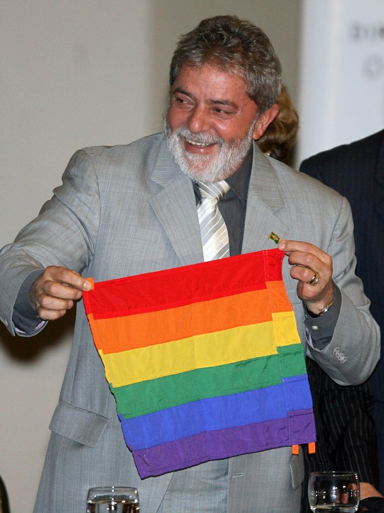 Brazilian President Luiz Inacio Lula da Silva holds a flag of the gay movement during the opening ceremony of the I National Conference of Gays, Lesbians and Transsexuals, on June 5, 2008, in Brasilia. AFP PHOTO/Joedson Alves (Photo credit should read JOEDSON ALVES/AFP/Getty Images)