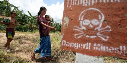 A Cambodian woman (C) carrying a baby walks by landmine awareness sign at O'Chhoeu Kram village in the former Khmer Rouge's stronghold Pailin near the Thai border some 375 kilometers north west of the capital Phnom Penh, 21 July 2007.  Nearly 30 years after the Khmer Rouge were pushed from power and following a decade of contentious negotiations, Cambodia appears poised to finally seek justice for the crimes committed during the regime's 1975-79 rule after prosecutors file cases against five former Khmer Rouge leaders .   AFP PHOTO / TANG CHHIN SOTHY (Photo credit should read TANG CHHIN SOTHY/AFP/Getty Images)