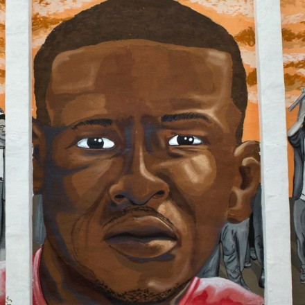A memorial mural to Freddie Gray, who died while in police custody just over one year ago, stands across the street from the spot where he was picked up by police in Baltimore, Maryland, April 23, 2016.  (photo by Allison Shelley)