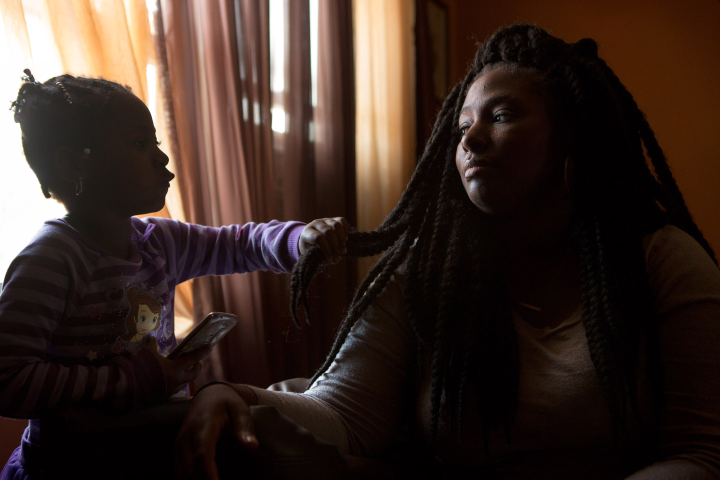 Kelly Holsey is comforted by her daughter Peyten Carter, 5, in the living room of her mother's home in the suburbs of Baltimore, Maryland, April 23, 2016. Holsey's fiancÈ Keith Davis Jr. was recently shot by police and is now in prison charged with murder-- all unfairly according to Holsey.  (photo by Allison Shelley)