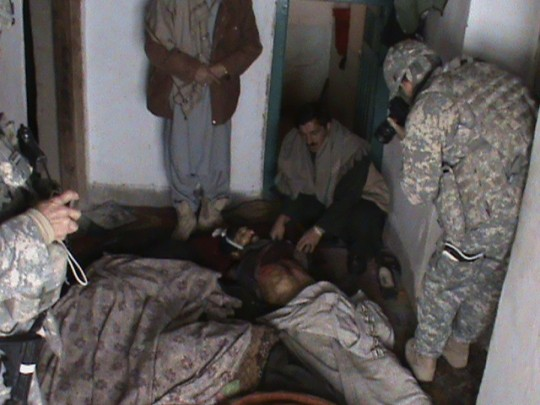 An U.S. soldier takes photograph of an Afghan man inside a room where five members of  an Afghan family were killed near Gardez, in Paktia province, south east Afghanistan, Friday, Feb. 12, 2010.  Afghan officials in Paktia province confirmed Friday they are investigating the deaths of five people in a home near the provincial capital of Gardez.  Police Chief Gen. Azizudin Wardak said the five  two men and three women were killed Thursday night during a party. (AP Photo)