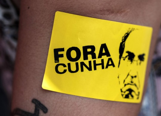 "A supporter of Brazilian President Dilma Rousseff demonstrates against her possible impeachment with a sticker reading ""Cunha out"", referring to the president of the Brazilian Chamber of Deputies, Eduardo Cunha, in Rio de Janeiro, Brazil on December 8, 2015. Brazil's opposition took the majority of seats Tuesday on a special congressional commission that will be first up to analyze the impeachment case against President Dilma Rousseff. AFP PHOTO / YASUYOSHI CHIBA / AFP / YASUYOSHI CHIBA        (Photo credit should read YASUYOSHI CHIBA/AFP/Getty Images)"