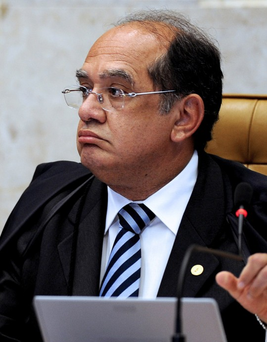 "Brazilian Supreme Court President Gilmar Mendes speaks during the trial of Italian Cesare Battisti in Brasilia, on November 18, 2009.  Brazil's Supreme Court is to resume on Wednesday its weighing of an extradition demand for an Italian ex-militant, with the outcome potentially creating a constitutional clash of powers. The court so far is evenly split on the case of whether to send Cesare Battisti, 54, back to Italy to serve a life sentence for murders committed in the 1970s.  A vote by chief justice Gilmar Mendes is to break a 4-4 deadlock among his colleagues.  The placards read ""To Extradite Cesare Is To Modernize The Inquisition"".  AFP PHOTO/Evaristo SA (Photo credit should read EVARISTO SA/AFP/Getty Images)"
