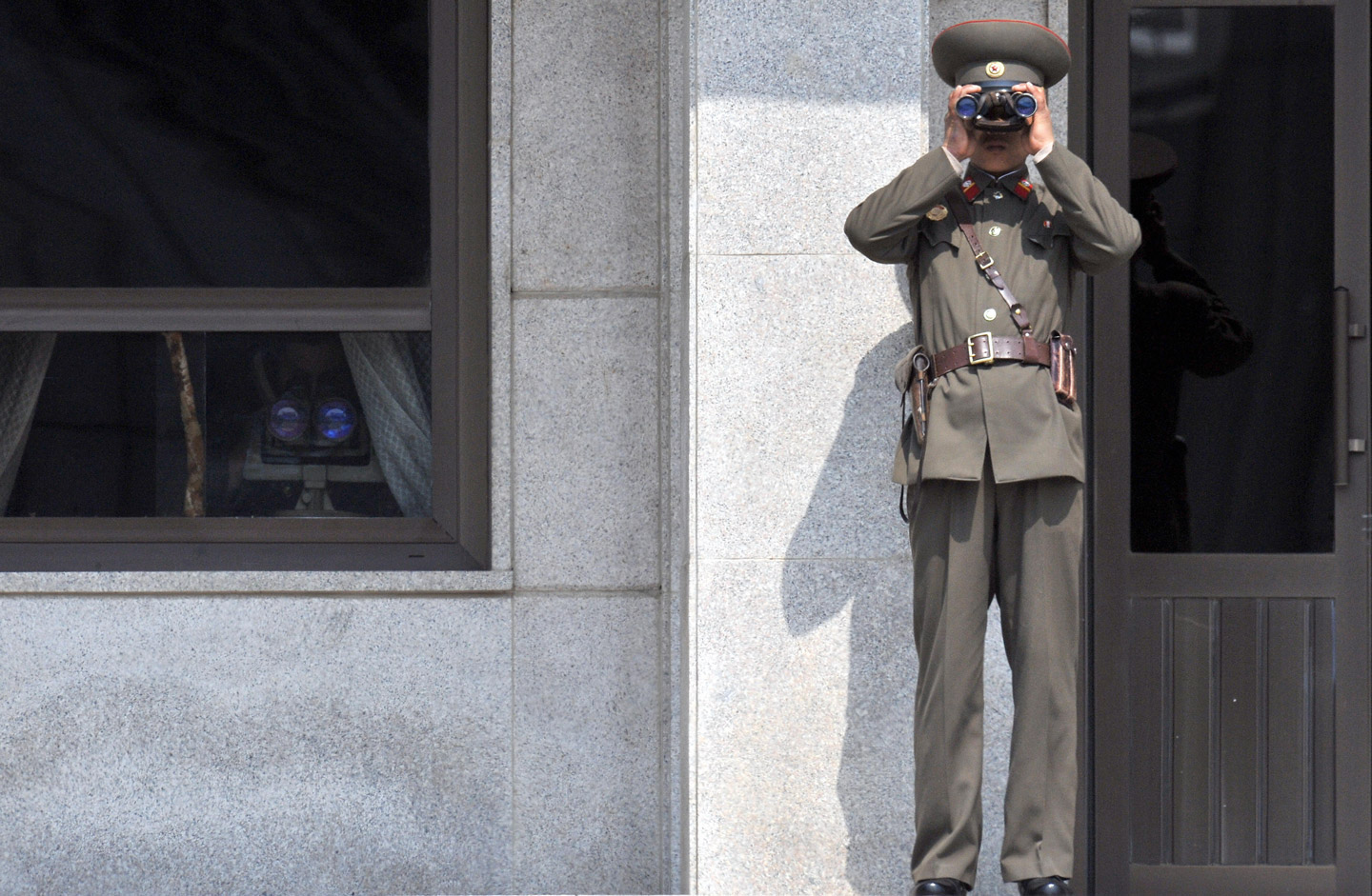 A North Korean soldier looks at the South side through binoculars at the truce village of Panmunjom in the demilitarized zone dividing two Koreas on April 9, 2009. North Korea's parliament re-elected Kim Jong-Il to the country's most powerful post, cementing his authority over the hardline communist state despite lingering health questions.  AFP PHOTO/JUNG YEON-JE (Photo credit should read JUNG YEON-JE/AFP/Getty Images)