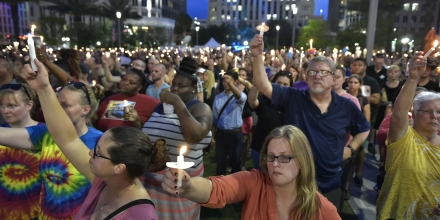 People hold candles during a vigil for the victims of the Pulse nightclub shooting, on June 13, 2016 at the Dr. Phillips Center for the Performing Arts in Orlando, Florida.The American gunman who launched a murderous assault on a gay nightclub in Orlando was radicalized by Islamist propaganda, officials said Monday, as they grappled with the worst terror attack on US soil since 9/11. / AFP / MANDEL NGAN (Photo credit should read MANDEL NGAN/AFP/Getty Images)
