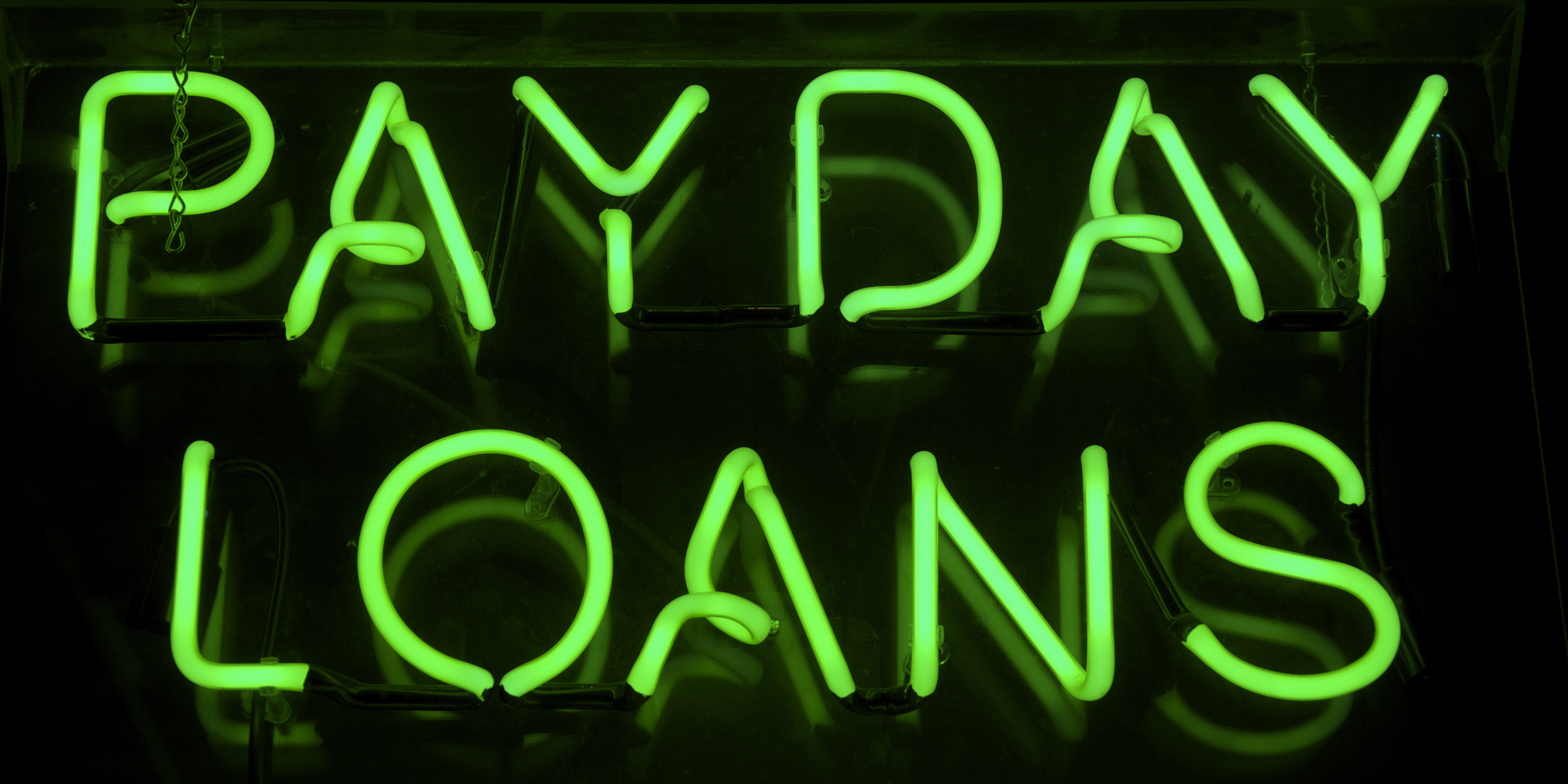 Payday Loans sign glows in green neon message on a black background