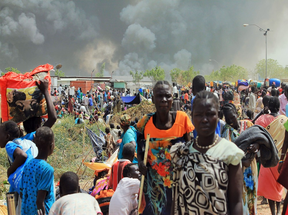 South Sudanese civilians flee fightings in the northeastern town of Malakal on February 18, 2016, where gunmen opened fire on civilians sheltering inside a United Nations base, killing at least five people, the latest in a string of atrocities in the war-torn nation, the UN said.Gunfire broke out in the base in Malakal in the northeast Upper Nile region on February 17, 2016 night, with clashes continuing on Thursday morning that left large plumes of smoke rising from burning tents in the camp which houses over 47,000 civilians. / AFP / Justin LYNCH (Photo credit should read JUSTIN LYNCH/AFP/Getty Images)