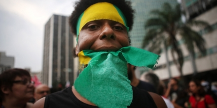 RIO DE JANEIRO, BRAZIL - MARCH 31: A protestor marches with Brazilian colors at a rally supporting President Dilma Rousseff on March 31, 2016 in Rio de Janeiro, Brazil. Embattled President Rousseff is facing impeachment charges amidst an economic and political crisis in Brazil. (Photo by Mario Tama/Getty Images)